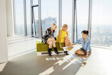 Three female architects in business meeting against urban skyline