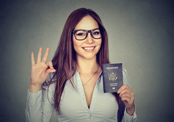 happy woman with USA passport giving ok sign