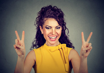 Smiling woman in yellow dress showing victory or peace sign