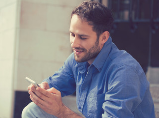 Happy man texting on phone sitting on stairs outside office