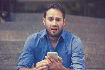 Anxious upset scared man looking at phone seeing bad news