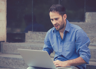 worried man working on laptop computer sitting outdoors