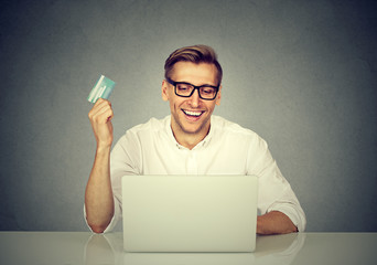 Online shopping payment. Man showing credit card using laptop