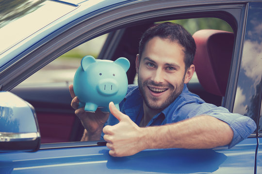 Man sitting inside new car holding piggy bank showing thumbs up