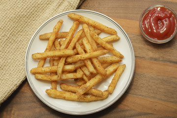 Fresh french fries on a wood background