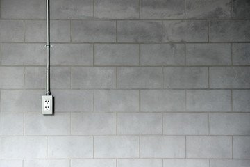 Steel pipe electric wire and plug on loft style cement wall back