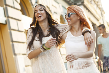 Young women in hippie style fashion laughing