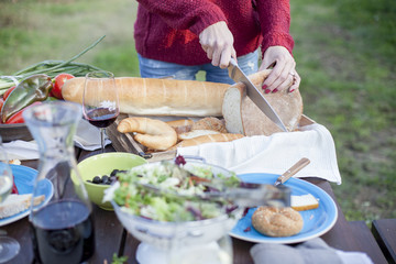 Person on garden party slicing loaf of bread