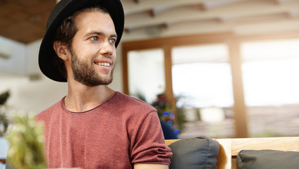 Isolated portrait of cheerful young bearded hipster smiling and having fun during nice conversation with his friends, sitting in modern restaurant interior. Stylish male relaxing indoors alone