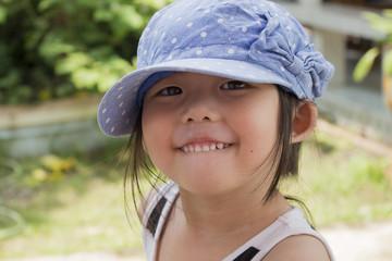 Little cute girl wearing a cap in garden. Smiling child