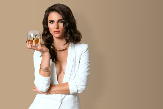 Sexy pose from a gorgeous model with a glass of whisky cocktail exotic and vogue