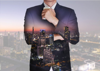 Double exposure of businessman stand up and think idea about business, cityscape, urban and street in the night or twilight as business and thoughtful concept.