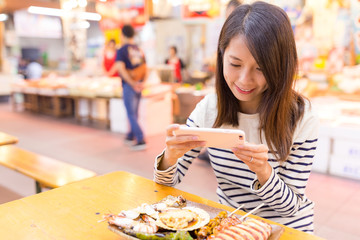 Woman taking photo before eating her seafood