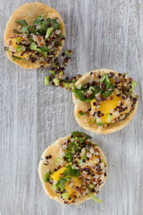 mango and quinoa salad served on crispy rice crackers.