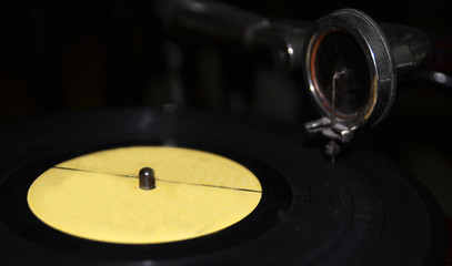 Black vinyl disc on a gramophone background