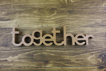 """The word """" TOGETHER"""" over the wooden board surface composition."""