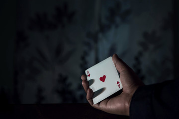 Ace Card in Hand, Chance or Risk of Love Concept, low-key lighting and selective focus on red heart