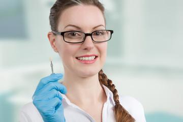 Zahnärztin prüft Zahnfarbe