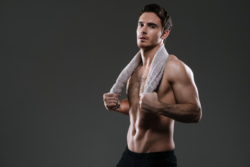 Handsome athlete standing in gym over grey background