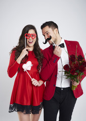 Playful couple with masks and bunch of roses