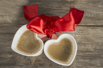 valentine's day/two cups of coffee heart shape with scarlet ribbon on old wooden background top view