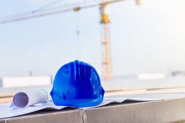 the blue safety helmet and the blueprint at construction site wi