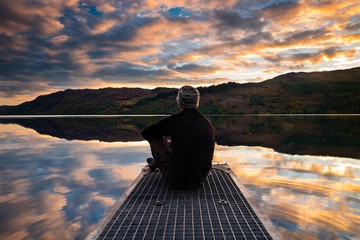 A man wearing a hat sits by a lake at sunset