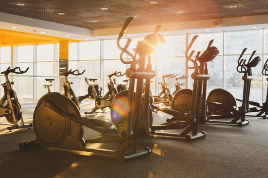 Modern gym interior with equipment, fitness exercise elliptical trainers