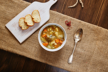 Vegetable soup on white bowl, cutting board with slices of bread