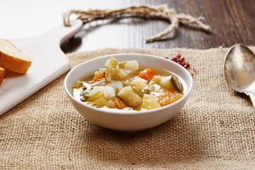 Vegetable soup on white bowl on wooden table