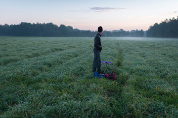 Young man standing with stool and backpack in misty meadow at da