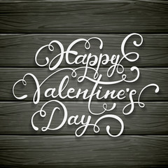 Happy Valentines Day on black wooden background