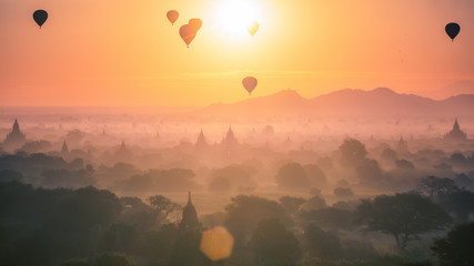 Hot air balloon over plain and pagoda of Bagan in misty morning