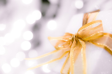 white Christmas gift box  with gold ribbon  and copyspace for y