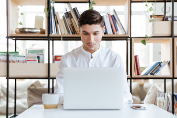 Concentrated man using laptop computer.