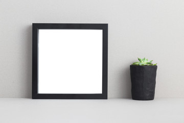 Photo frame and succulent on a shelf.