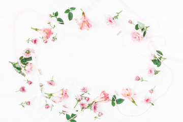 Flowers composition. Frame made of pink flowers and leaves. Top view, flat lay