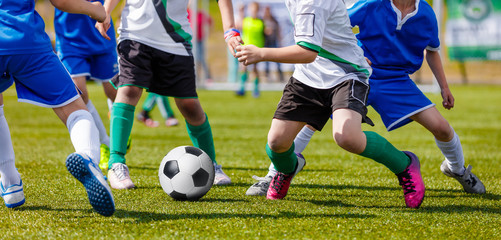 Young Boys Soccer Players Kicking Football on the Sports Field. Running Footballers in Blue and White Jerseys. Soccer Horizontal Background