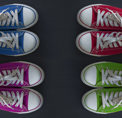 Four pairs of colorful sneakers youth on a black surface