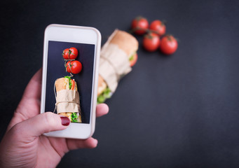 Human hand using smartphones to take photos of sandwich
