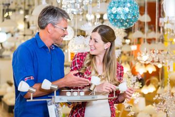 Kundin bittet einen Verkäufer in Elektroabteilung eines Baumarkts um Hilfe bei Auswahl von Leuchten