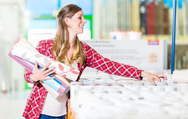 Junge Frau beim Kauf von Tapeten im Heimwerkermarkt