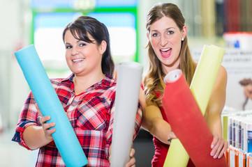 Junge Frauen im Baumarkt bei Auswahl von Tapeten für Do-it-yourself-Renovierung