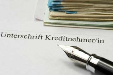 Ein Kreditvertrag, Füllfederhalter und Euro Geldscheine