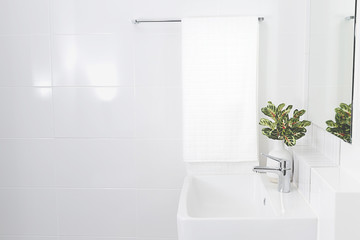 White sink and flower vase in bathroom