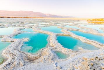 View of Dead Sea coastline. Salt crystals at sunset. Texture of Dead sea. Salty sea shore