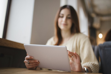 Modern woman using tablet pc in a cafe, focus on foreground