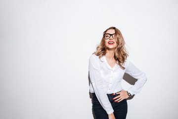 Woman in eyeglasses standing and posing with hand on hips