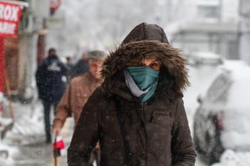 Bucharest, Romania, December 29, 2014: A woman walks on the street during a blizzard in Bucharest.