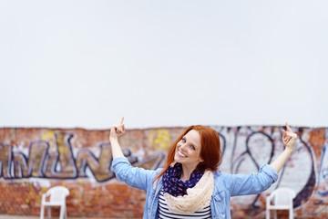 glückliche frau zeigt mit beiden händen auf ein weißes plakat